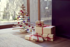 Wooden Christmas Tree Decorated with Colorful Baubles and Christmas Presents next to it.